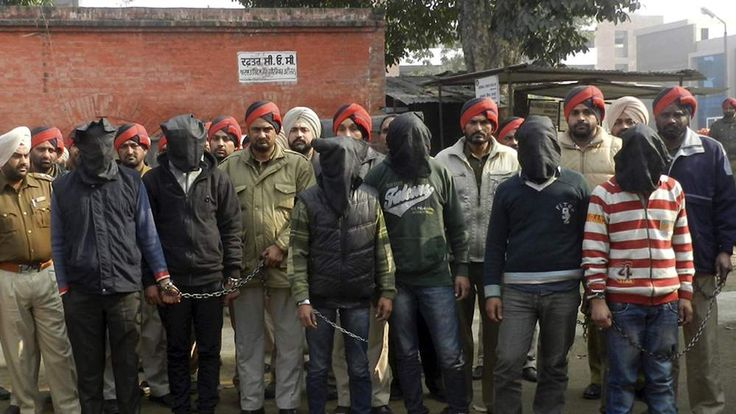Policemen stand with six men, with their faces covered in black sheets, who are suspected in a gang rape of a bus passenger in Punjab, India