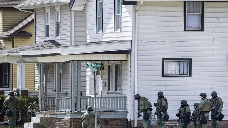 SWAT officers surround the house