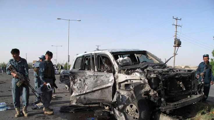 Afghan policemen inspect the site of a suicide car bomb attack in Helmand province