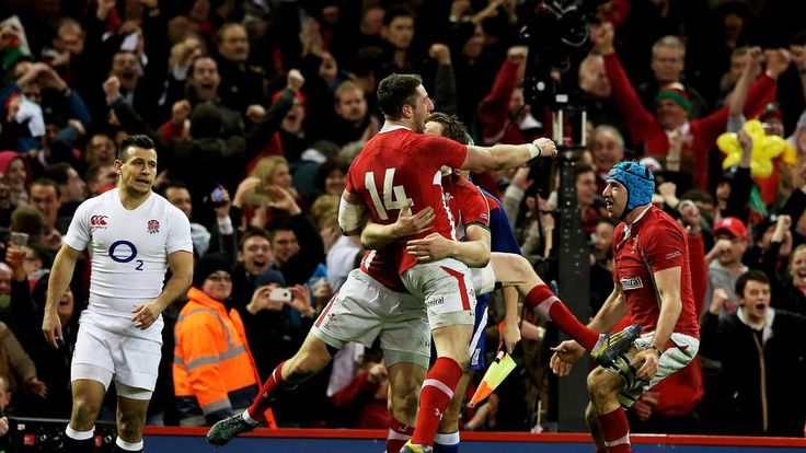 Alex Cuthbert (14) of Wales celebrates with teammates Dan Biggar (L) and Justin Tipuric (R)