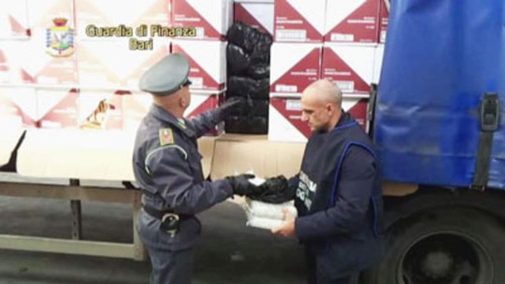 Italian officials unloading white packages of heroin, wrapped in black plastic, stashed in between boxes of breadsticks.