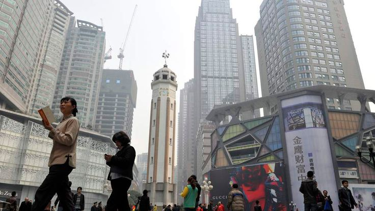 Residents walk past the Chongqing People's Liberation Monument, which was built in 1945 to commemorate the victory over the Japanese during the World War II, in Chongqing municipality