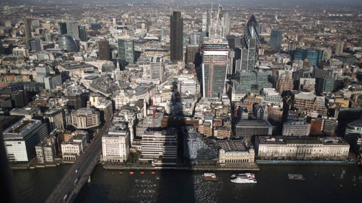 The shadow of the Shard falls over the River Thames and The City of London
