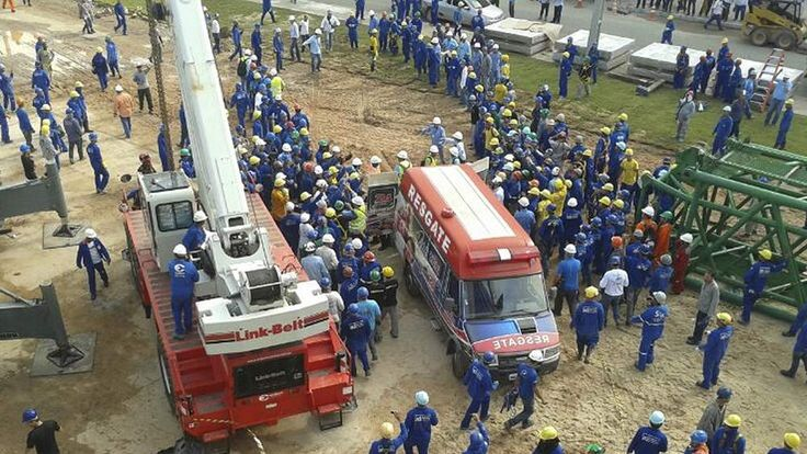 Workers surround an ambulance as a 55-year-old Portuguese worker is rushed to hospital