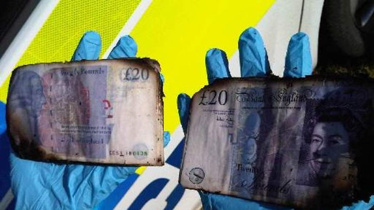 A forensic officer holds two of the British notes