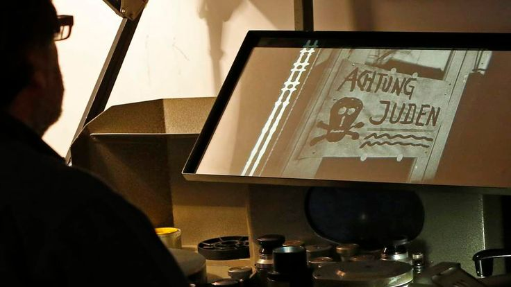 """Bruno Mestdagh, the head of the digital collection at the Cinematheque Royale de Belgique, looks at footage of the 1934 U.S. anti-Nazi film, """"Hitler's Reign of Terror"""", in Brussels"""