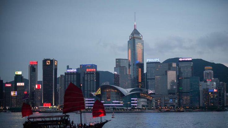 A junk sails on Victoria Harbour in front of the city's skyline in Hong Kong