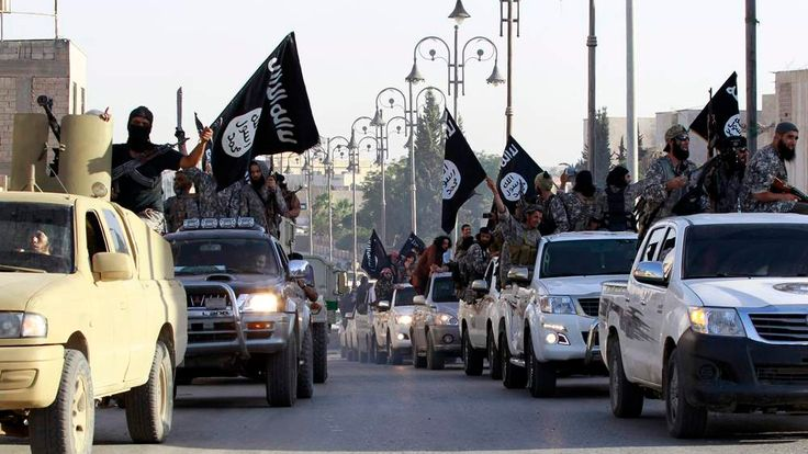 Militant Islamist fighters parade on military vehicles along the streets of northern Raqqa province of Syria