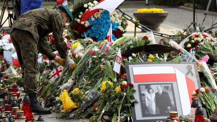 A Polish soldier arranges flowers left by mourners next to a portrait of late Polish President Lech Kaczynski and his wife Maria outside the Presidential Palace
