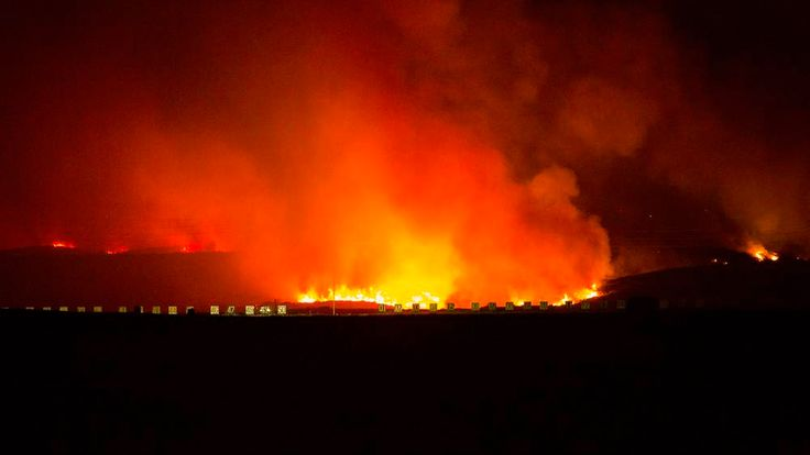 The Las Pulgas Fire is seen burning near military structures at Camp Pendleton, California
