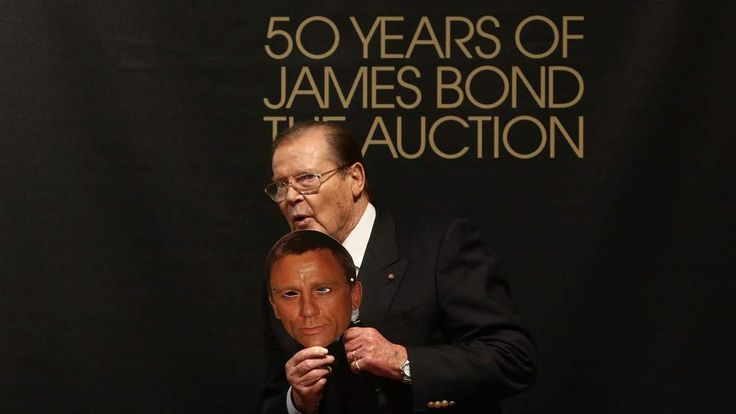 Sir Roger Moore holding a mask of current James Bond actor Daniel Craig at Christie's 50 Years of James Bond Sale