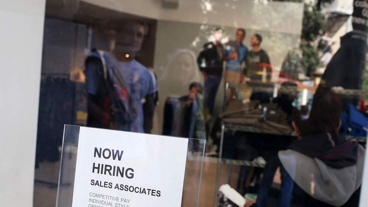 "A ""now hiring"" sign is posted in the window of a store in San Francisco."