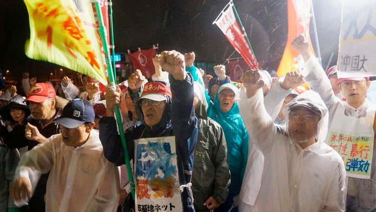 Protesters raise their fists and shout slogans in front of the gate of the US base Camp Zukeran on the southern Japanese island of Okinawa