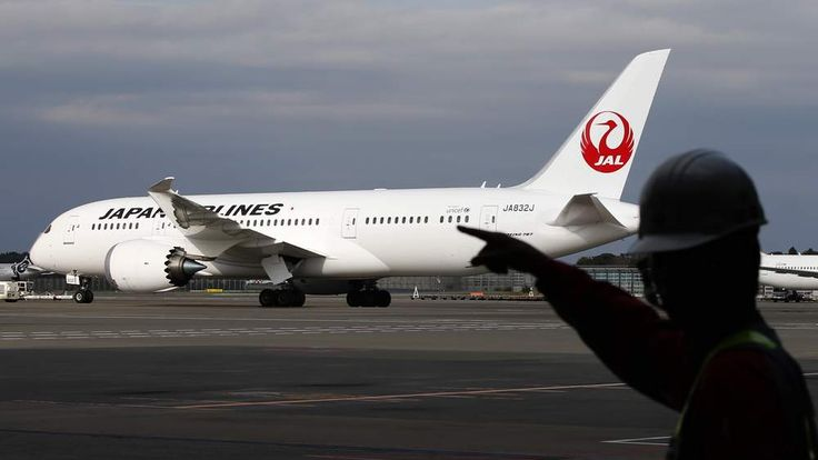 A staff of Japan Airlines' (JAL) walks past one of the company's Boeing Co's 787 Dreamliner plane at Narita international airport