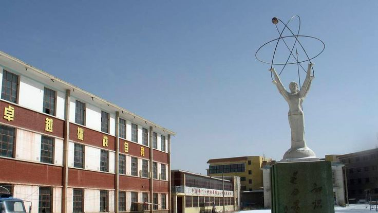 A statue is seen near an abandoned apartment block on the outskirts of the oil-producing town of Yumen, Gansu province