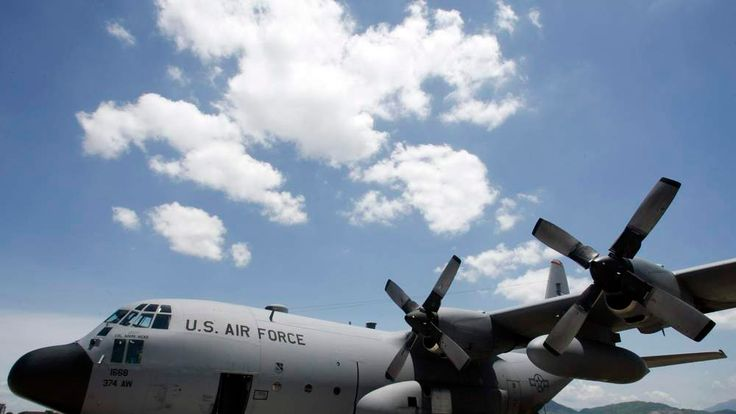 U.S. military personnel stand near a C130 aircraft before a repatriation ceremony at Danang city's international airport