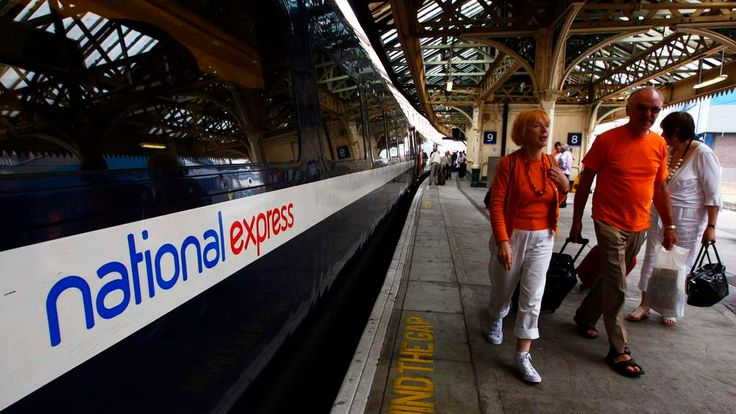 Passengers walk past a National Express East Coast line train at Waverley Station in Edinburgh, Scotland