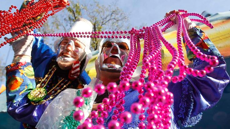 Members of the Krewe of Thoth throw beads to Mardi Gras revelers