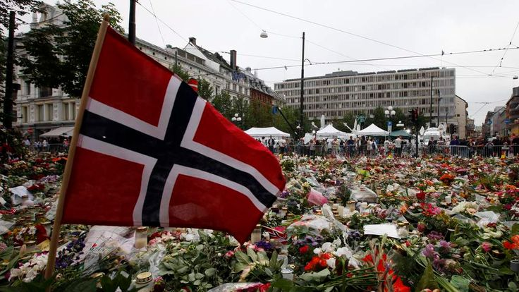 A Norwegian flag is placed in a sea of flowers and candles which are placed in memory of those killed in last Friday's bomb and shooting attack, in front of Oslo Cathedral