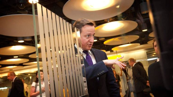 Britain's Prime Minister David Cameron talks to UK Border Agency officials during a visit to Terminal 5, at Heathrow Airport, west of London
