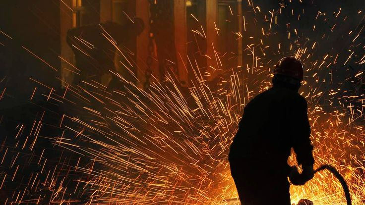 Labourers work at a steel manufacturing plant