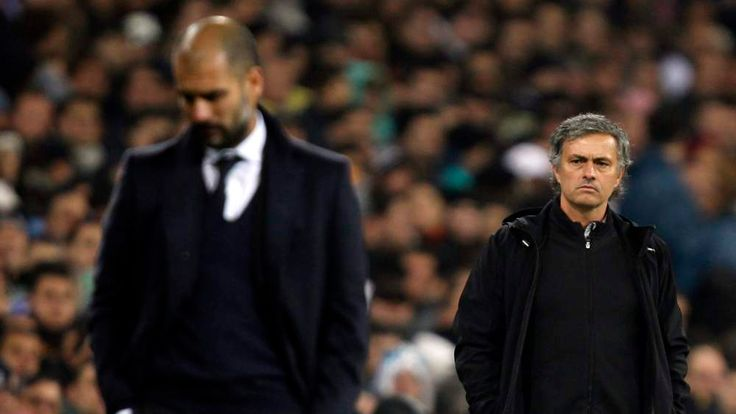 """Real Madrid's coach Jose Mourinho looks at  Barcelona coach Pep Guardiola after Xavi Hernandez goal during their Spanish first division soccer match, the """"Clasico"""",  at the Santiago Bernabeu stadium in Madrid"""