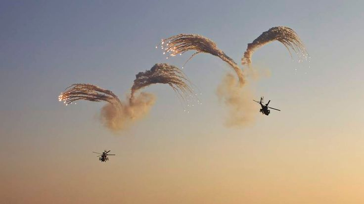 Israeli Apache helicopters release flares during during an air force pilots' graduation ceremony in southern Israel