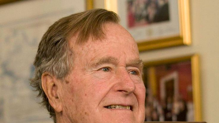 Former President Bush smiles as he listens to Republican presidential candidate Romney speak in Houston