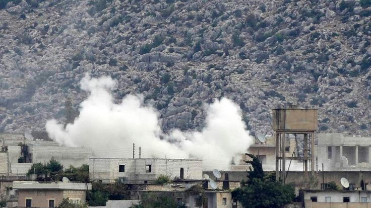 Smoke, caused by mortar bombs and gunfire during clashes between the Syrian Army and rebels, rises from the Syrian border town of Azmarin