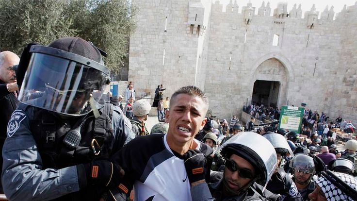 Israeli border police officers detain a Palestinian demonstrator
