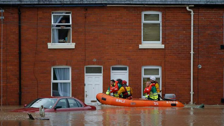A man looks from a house window as rescue workers ride in a boat down a flooded street in St Asaph