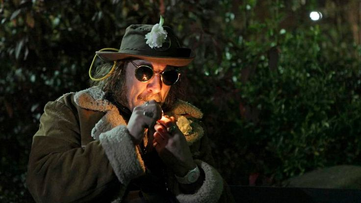 """A man, who identified himself as """"Professor Gizmo,"""" lights up a pipe minutes before the law legalizing the recreational use of marijuana went into effect in Seattle, Washington"""