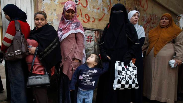 A boy stands with his mother as she queues outside a polling center to vote during a referendum on Egypt's new constitution in Cairo