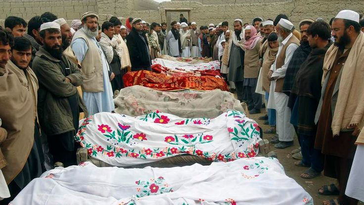 Afghan villagers stand around the bodies of girls who were killed by an explosion in Jalalabad