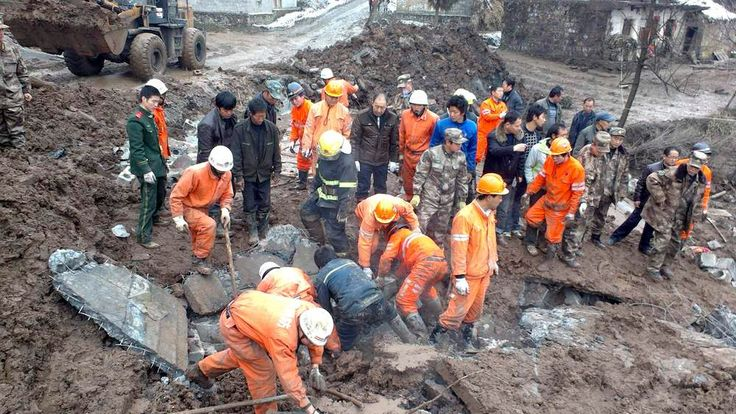 Rescuers search for victims after a landslide hit Zhenxiong county