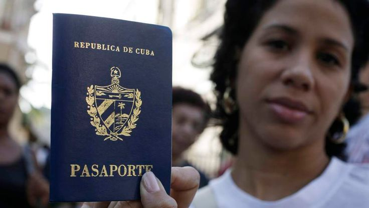 A woman shows her new passport while standing with others outside a passport office in Havana