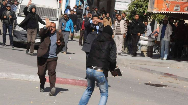 Protesters plead with a plainclothes policeman not to shoot plastic bullets at them during a demonstration in Gafsa