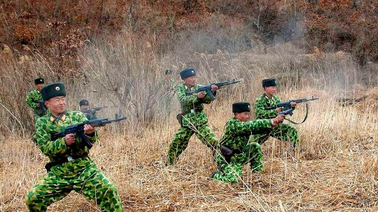 North Korean soldiers with weapons attend military training in an undisclosed location