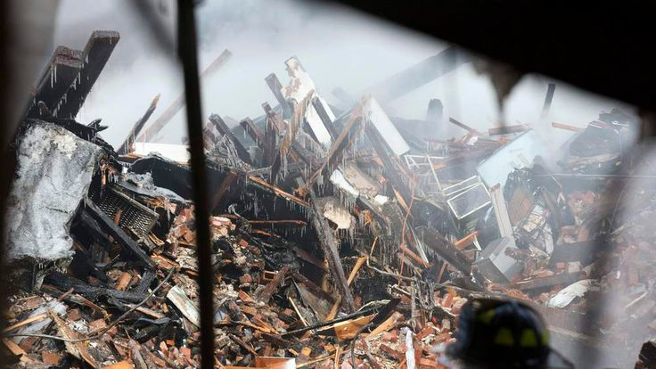 New York City emergency responders search through the rubble at the site of a building explosion in the Harlem section of New York