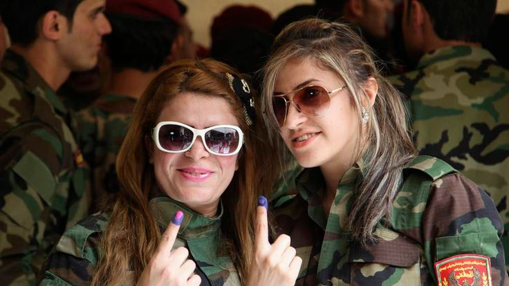 Kurdish security forces personnel show their ink-stained fingers after casting their votes at a polling station, during early voting for the parliamentary election in Arbil, in Iraq's Kurdistan region