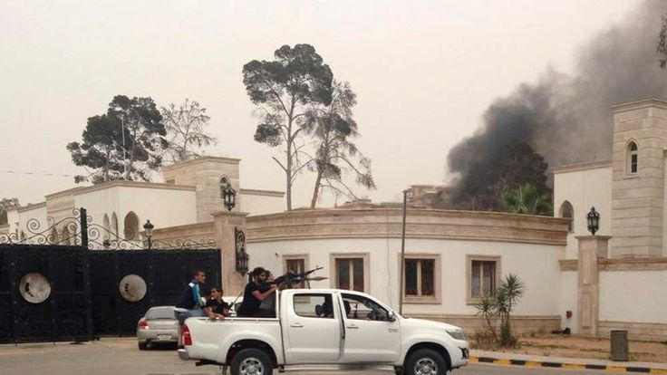 Armed men aim their weapons from a vehicle as smoke rises in the background near the General National Congress in Tripoli.
