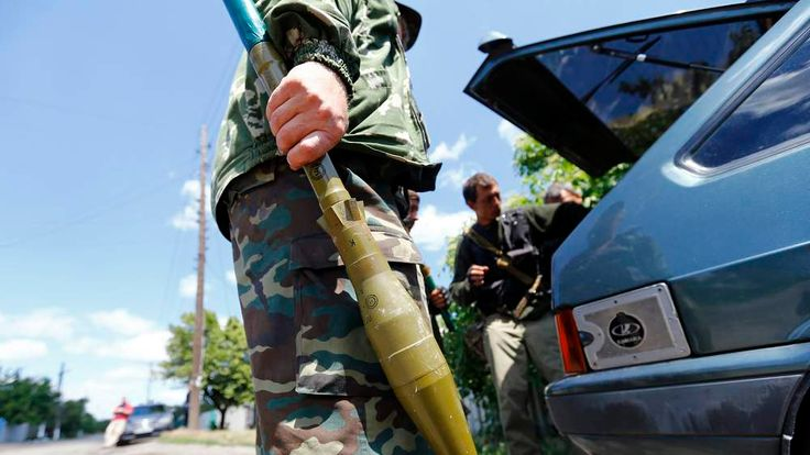 Armed Pro-Russian separatists gather near a car before driving to the battle line in Seversk