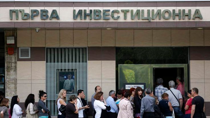 People queue outside a branch of Bulgaria's First Investment Bank, in Sofia, on June 27