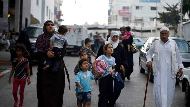 Palestinians flee their houses during heavy Israeli shelling at the Shejaia district in Gaza City