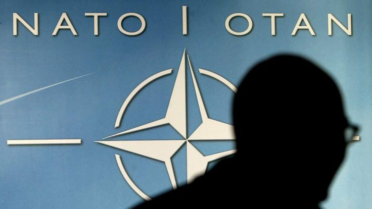 A MAN WALKS PAST THE NATO LOGO DURING A NATO DEFENCE MINISTERS MEETINGIN BRUSSELS.