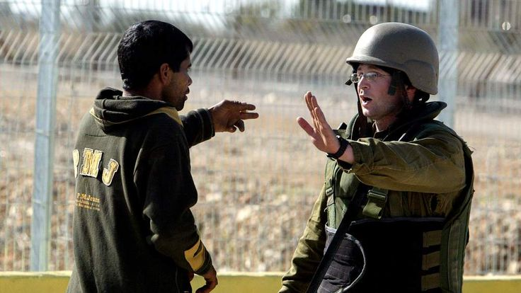 ISRAELI SOLDIER AND PALESTINIAN MAN GESTURE AT CHECKPOINT NEAR WESTBANK CITY OF QALQILYA.