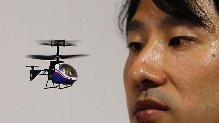 """An employee of Japanese toymaker CCP Co. looks at the company's """"NANO-FALCON"""" at the International Toy Show in Tokyo"""