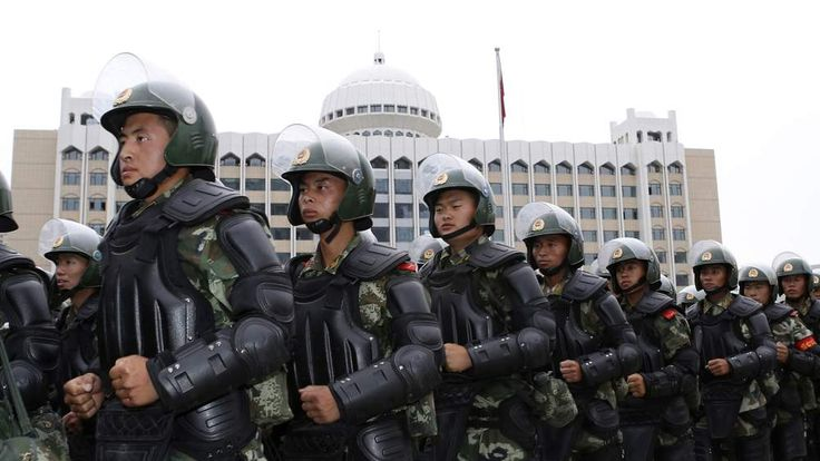 Armed paramilitary policemen run in formation during a gathering to mobilize security operations in Urumqi, Xinjiang