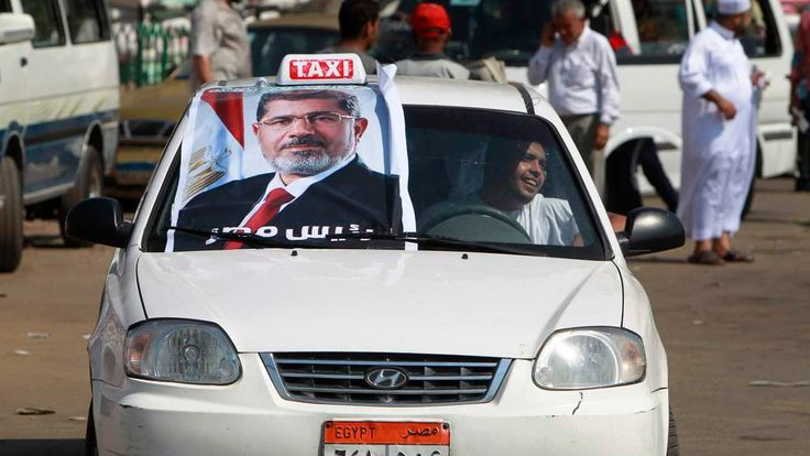 A supporter of Mohammed Morsi displays a picture of the ousted president on his car