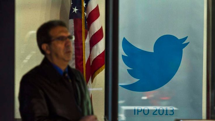 A man walks past a Twitter banner while leaving JP Morgan headquarters, before Twitter's IPO in New York